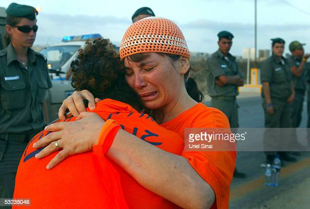 Israeli settlers hug each other at a checkpoint preventing nonresident from entering the Southern Gaza settlement of Gush Katif July 14 2005 at the...