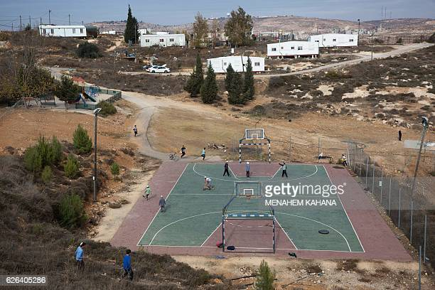 TOPSHOT Israeli settlers play in the settlement outpost of Amona which was established in 1997 in the Israelioccupied West Bank on November 29 2016...