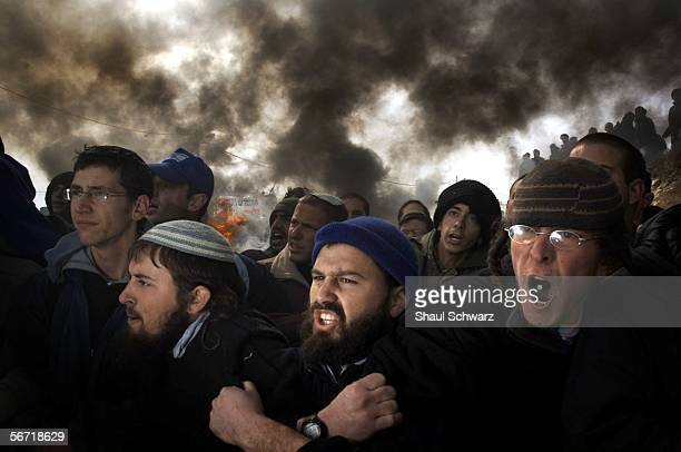 Israeli settlers stand arm in arm Israeli riot police February 1 2006 in the West Bank outpost of Amona The residents of Amona compose one of...