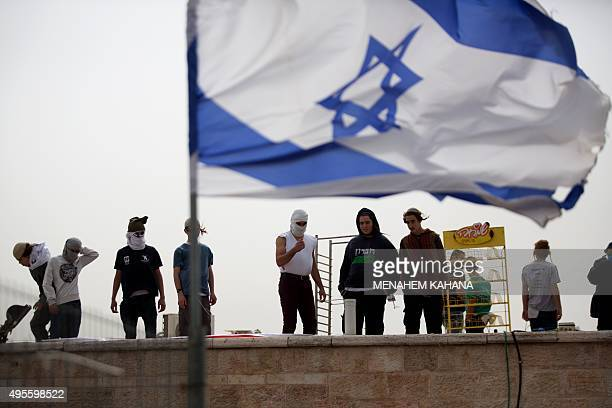 Israeli settlers stand on the roof of a synagogue in the West Bank settlement of Givat Zeev north of Jerusalem on November 4 2015 Hundreds of Israeli...