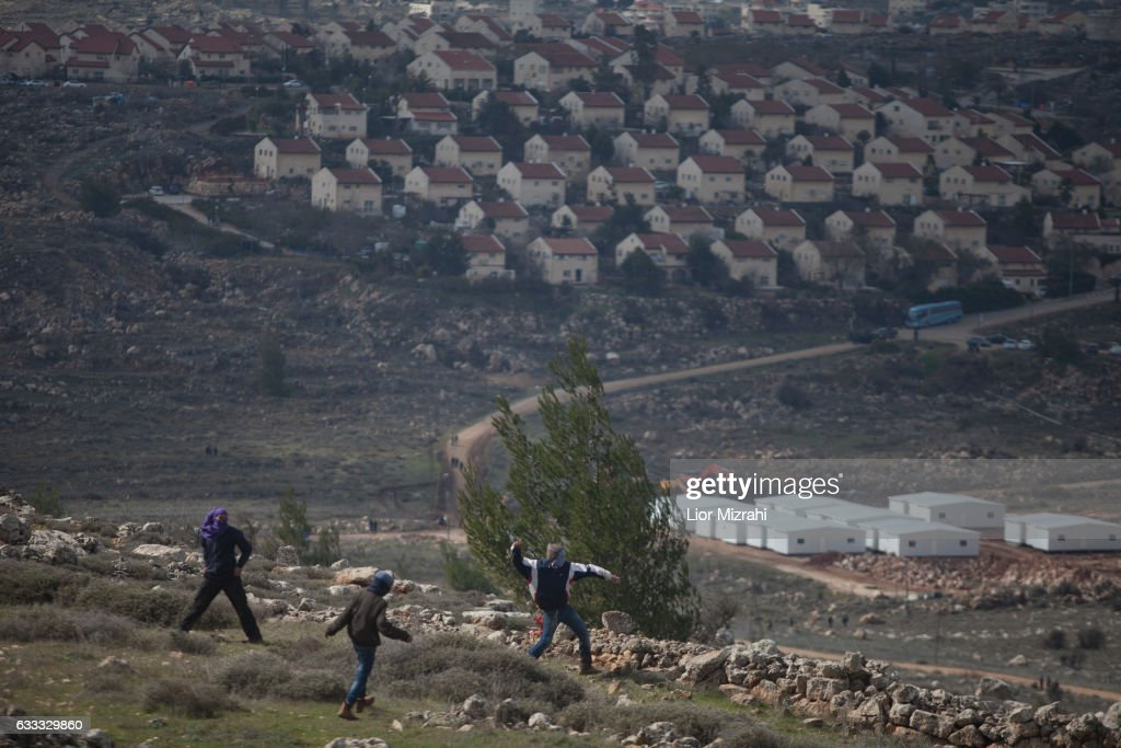 Israeli settlers throw stones on security forces during the evacuation of the illegal Jewish settlement on February 1, 2017 in Amona, West Bank. Israeli Security forces have started evacuating residents from the illegal outpost of Amona in the West Bank on Wednesday, after hundreds of youths streamed into the outpost to fight the evacuation.