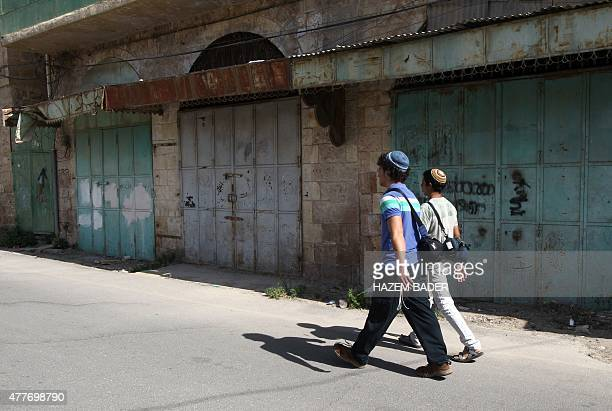 Israeli settlers walk past Palestinian shops which have been closed since the second 'intifada' or uprising in 2000 after Israel approved the...