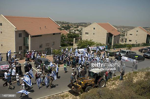 Israeli settlers wave their national flag as they participate in a march from the Ulpena outpost nearby the West Bank settlement of Beit El to...