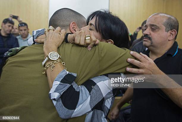 Israeli soldier Elor Azaria who shot dead a wounded Palestinian assailant is embraced by his mother as he awaits for the verdict in his case at the...