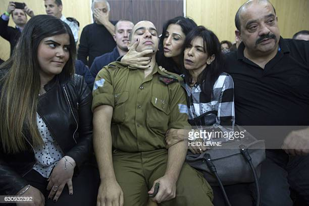 Israeli soldier Elor Azaria who shot dead a wounded Palestinian assailant sits with his family as he awaits for the verdict in his case at the...