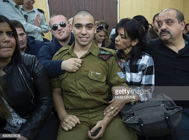 Israeli soldier Elor Azaria who shot dead a wounded Palestinian assailant sits with his parents as he awaits for the verdict in his case at the...