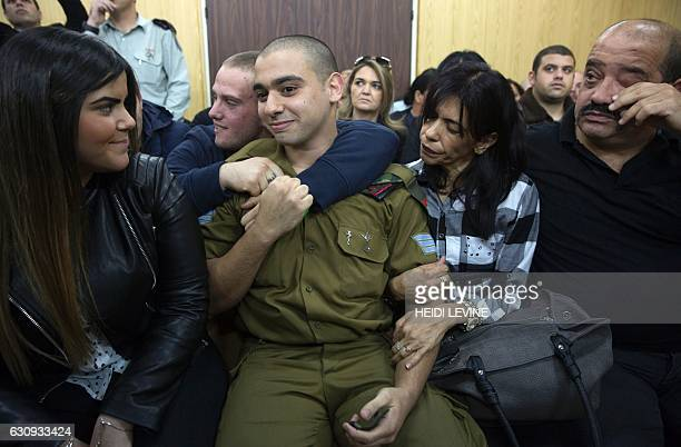TOPSHOT Israeli soldier Elor Azaria who shot dead a wounded Palestinian assailant sits with his parents and his girlfriend Orel as he awaits for the...