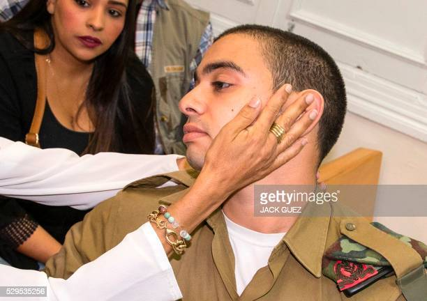Israeli soldier Elor Azaria who was caught on video shooting a wounded Palestinian assailant in the head as he lay on the ground is comforted by his...