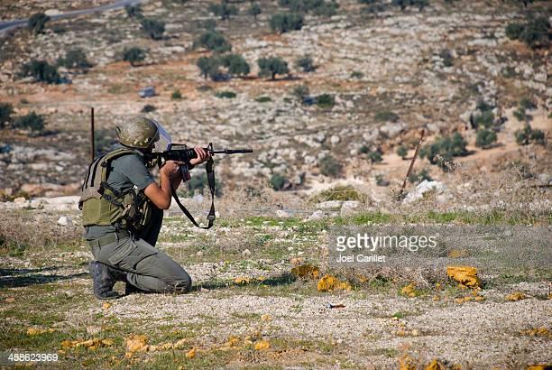 Israeli soldier firing weapon in West Bank village of Bil'in