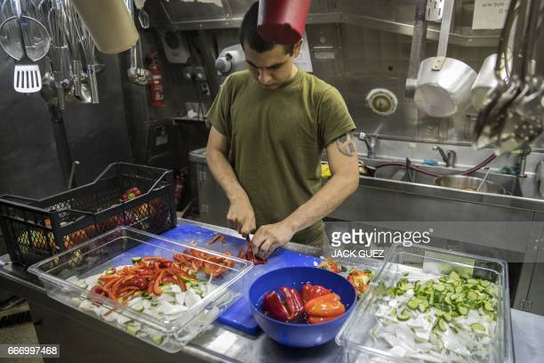 A Israeli soldier onboard the Israeli vessel Saar 5 Class Corvette 'INS Hanit' prepares food during the 'Novel Dina 17' exercise in the Mediterranean...