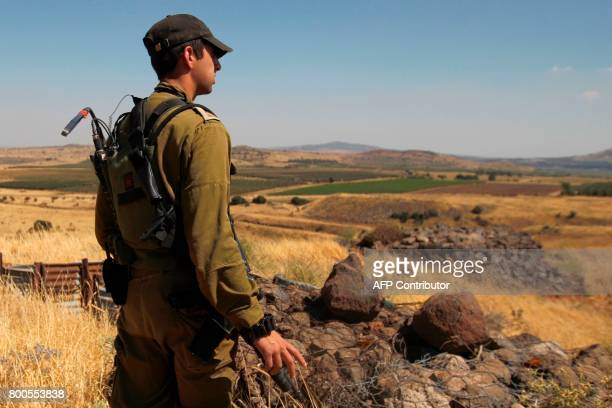 A Israeli soldier patrols near the border with Syria after projectiles fired from the wartorn country hit the Israeli occupied Golan Heights on June...