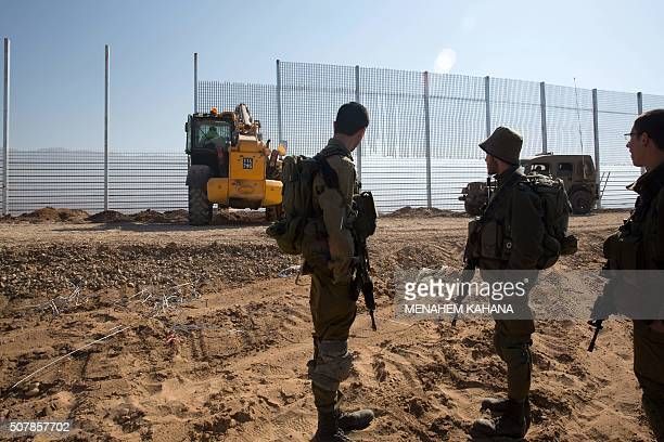 Israeli soldieres stand guard as workers erect a new fence along Israel's border with Jordan in the Arabah valley some 30 Kilometres north to the...