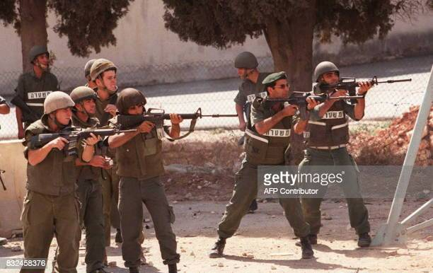 Israeli soldiers aim at Palestinian stonethrowers during a protest at an Israeli army checkpoint near Ramallah in the West Bank 25 September More...