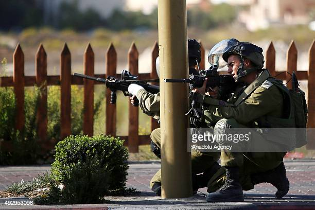 Israeli soldiers aim their rifles as Palestinians stage a protest near the Jewish settlement of Beit El north of Ramallah on October 16 2015...