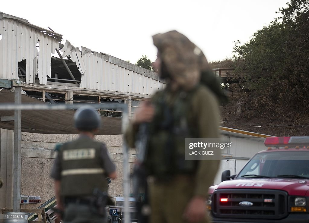 Israeli soldiers and rescue workers arrive to inspect the damage after a mortar round reportedly fired from Syria hit a winery in the Israeli-occupied Golan Heights, on August 27, 2014