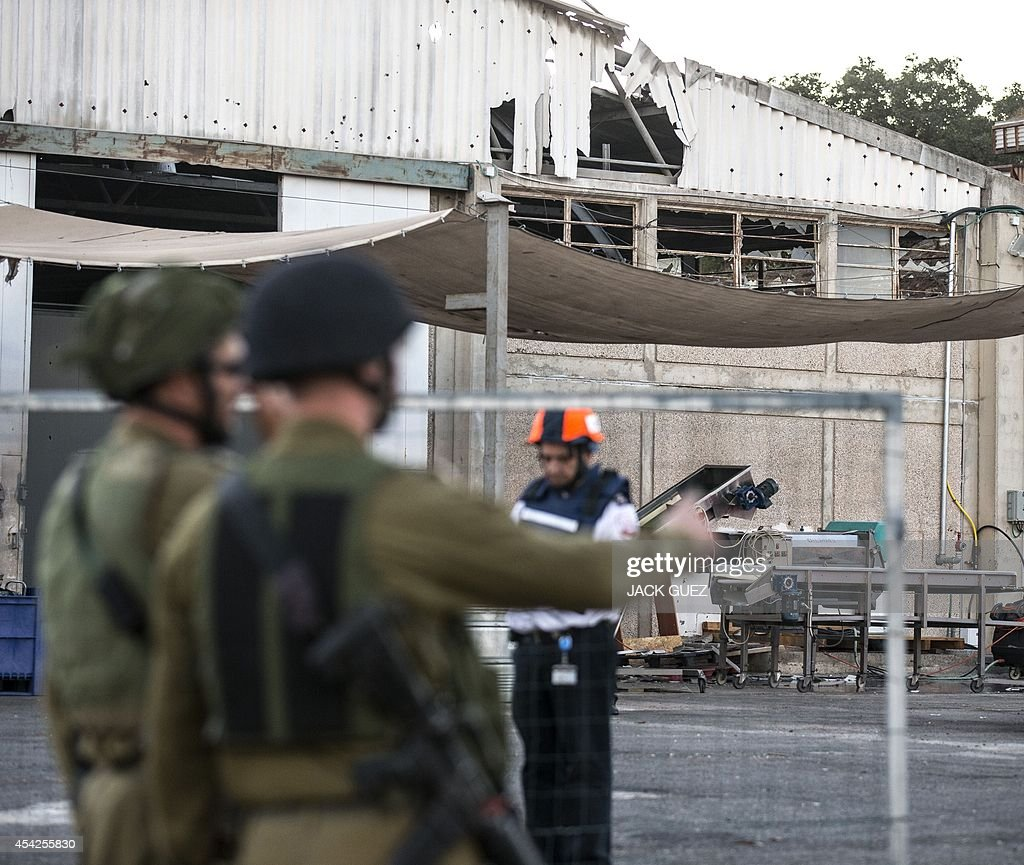 Israeli soldiers and rescue workers arrive to inspect the damage after a mortar round reportedly fired from Syria hit a winery in the Israeli-occupied Golan Heights, on August 27, 2014. According to an Israeli army colonel there has been extensive fighting' on the Syrian side of the 1967 ceasefire line since early today which had resulted in several instances of 'errant fire.' Rebel fighters, including some from Al-Qaeda affiliate Al-Nusra Front, captured the Syrian side of the sole crossing over the armistice line earlier today in deadly fighting with government troops, the Britain-based Syrian Observatory for Human Rights said.