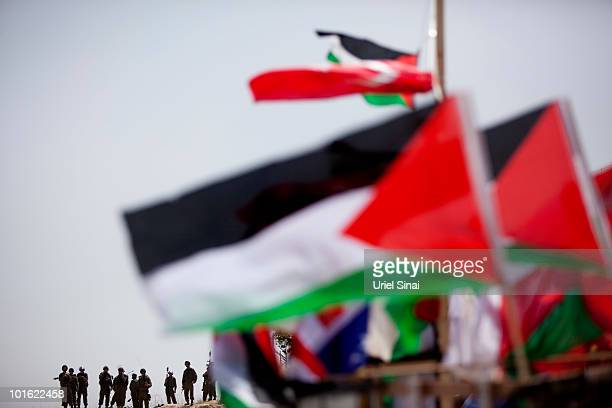 Israeli soldiers approach a replica of the Gaza aid flotilla used by Palestinians near an Israeli barrier as they object to Israel's attack on the...