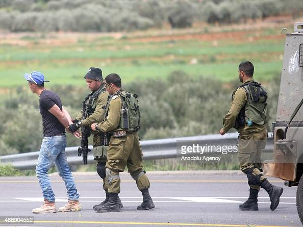 Israeli soldiers arrest a man after a Palestinian man who was killed by Israeli soldiers after stabbing two Israelis in the West bank village of...