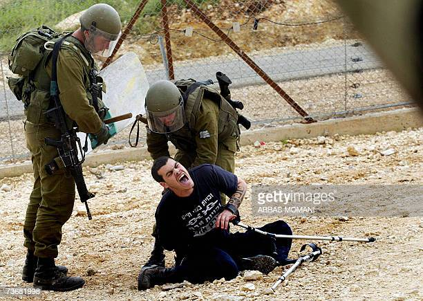 Israeli soldiers arrest a man on crutches during the weekly protest by Palestinian and foreign activist against the construction of the controversial...