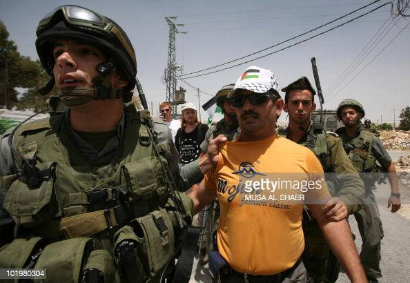 Israeli soldiers arrest a Palestinian protester after he burnt the Israeli flag during a demonstration by Palestinian Israeli and foreign peace...