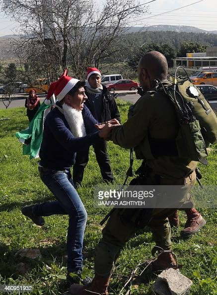 Israeli soldiers arrest a Palestinian young protester during clashes on January 1 2015 at Hawara checkpoint east of the West Bank city of Nablus...