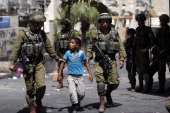 Israeli soldiers arrest a young Palestinian boy following clashes in the center of the West Bank town of Hebron on June 20 2014 Israeli soldiers...