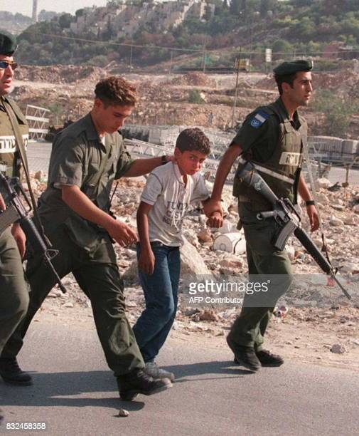 Israeli soldiers arrest a young Palestinian stone thrower during a protest at an Israeli army checkpoint near the West Bank town of Ramallah 25...
