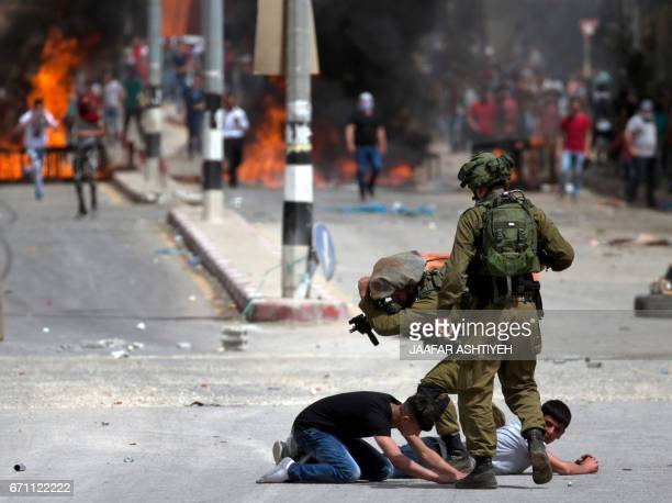 TOPSHOT Israeli soldiers arrest Palestinian demonstrators amid clashes in the West Bank village of Beita southeast of Nablus city after a protest...