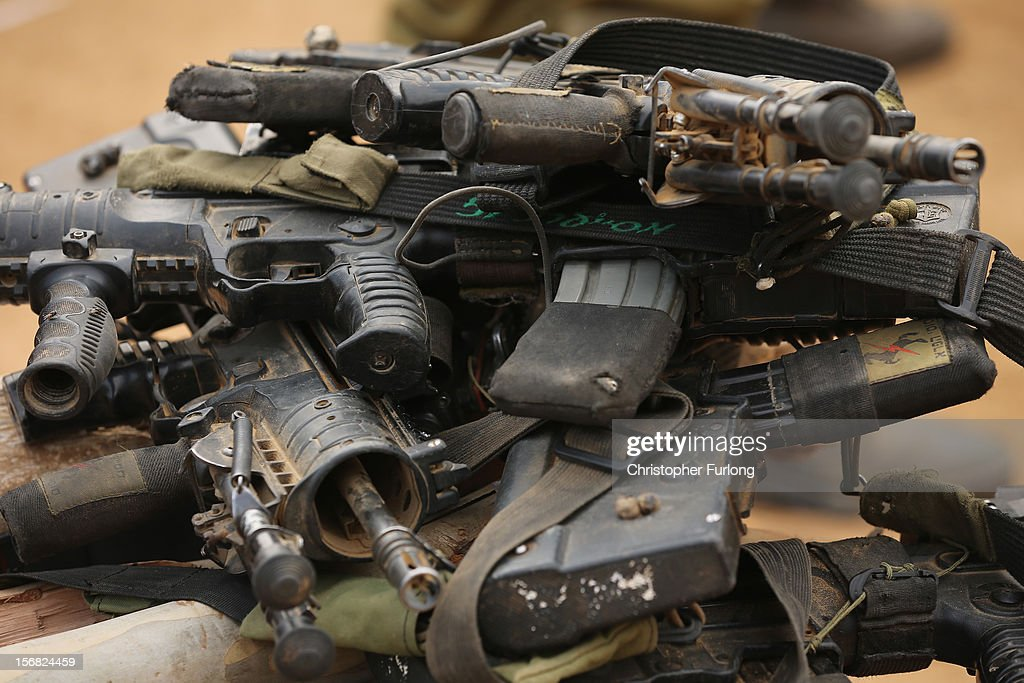 Israeli soldiers assault rifles lay piled on the ground as the cease fire in the recent conflict comes into effect at the border with the Gaza Strip on November 22, 2012 close to the northern Gaza Strip border with Israel. The ceasefire between Israel and Hamas appears to be holding despite rockets being fired on Israel from Gaza. During the night the IDF reportedly arrested a number of 'terror operatives' in the West Bank in continued efforts to restore peace in the region.