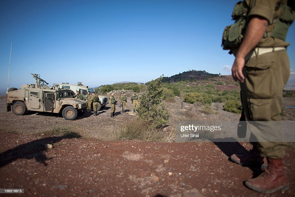 Israeli soldiers at the border line with Syria at the Israeli-annexed Golan Heights, overlooking the Syrian village of Breqa on November 13, 2012 in the Golan Heights. Tension remains high in the disputed Golan Heights after Israeli Defence Forces retaliated after mortar shells were fired into Israeli territory from Syria.