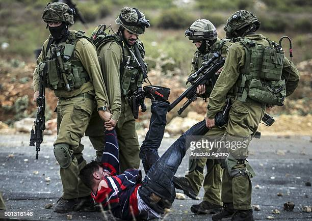 Israeli soldiers beat up Palestinians as they take some protesters into custody during a protest against preventing Palestinians from entering the...