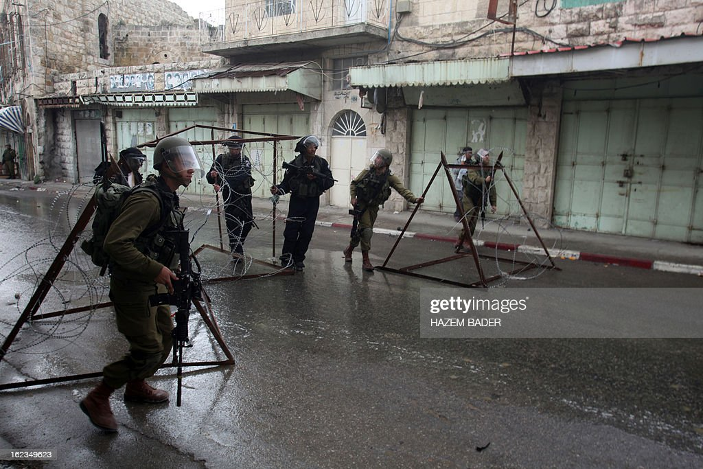 Israeli soldiers block al-Shuhada street during clashes with Palestinian protestors who are demanding the right of access to the street that can only be used by Israeli settlers, in the West Bank town of Hebron on February 22, 2013. AFP PHOTO / HAZEM BADER