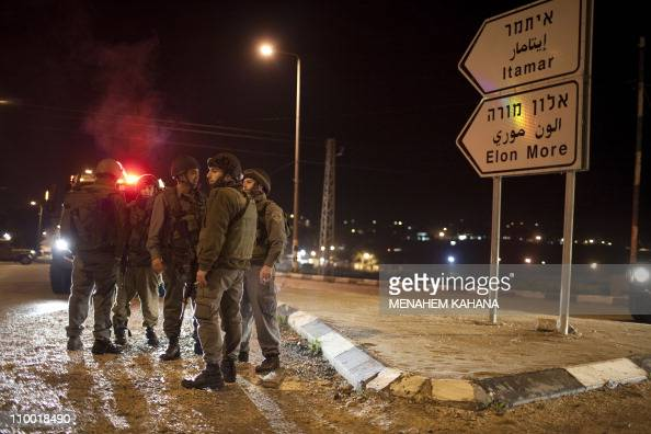 Israeli soldiers block the road in the Hawara checkpoint south of the West Bank city of Nablus on March 122011 after a Palestinian killed five...