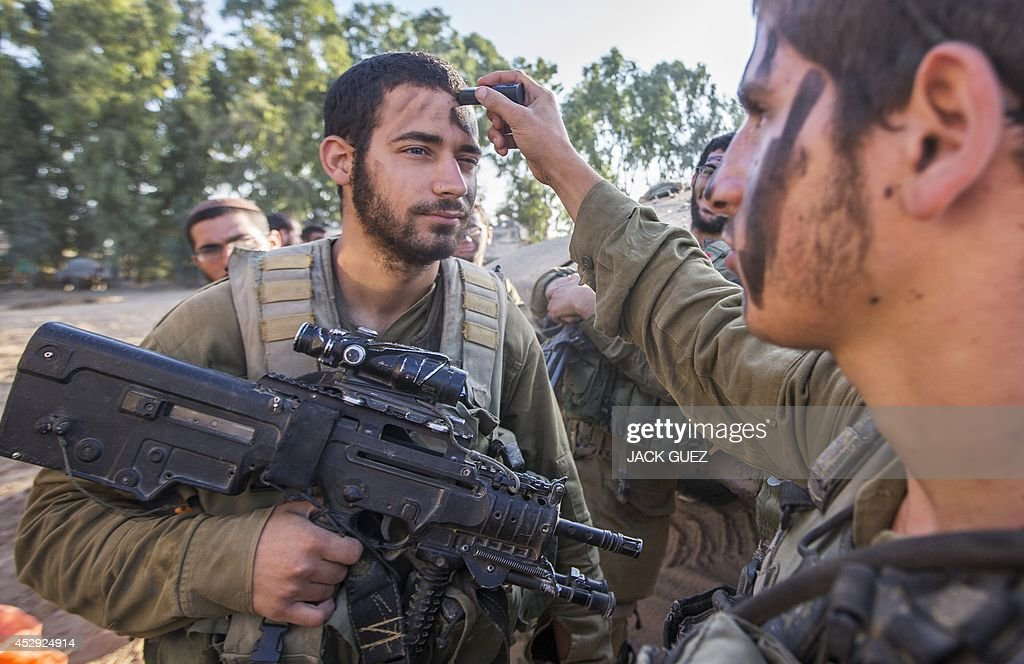 Israeli soldiers camouflage their faces at an army staging area along Israel's border with the Gaza Strip on July 30, 2014, as they prepare to enter the Gaza Strip. Israel agreed to observe a four-hour lull in Gaza several hours after a deadly strike on a school killed 16, drawing a furious response from a UN refugee agency.