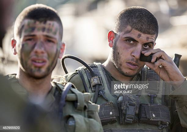Israeli soldiers camouflage their faces at an army staging area along Israel's border with the Gaza Strip on July 30 as they prepare to enter the...