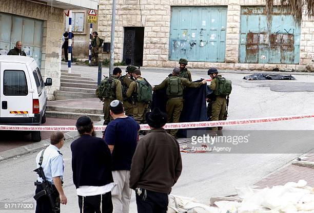 Israeli soldiers carry 2 dead bodies Palestinians after they have allegedly tried to stab Israeli soldiers in Hebron West Bank on March 24 2016