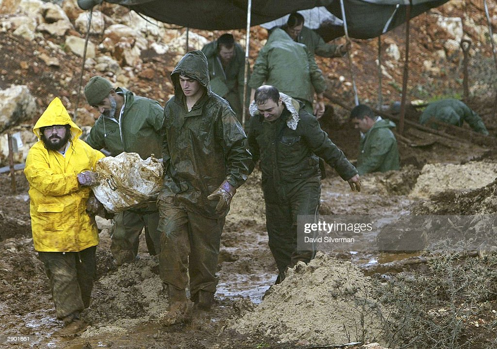 Israeli soldiers carry the exhumed body of one of 59 Lebanese through the mud from the army's Enemy Graveyard January 26 2004 near Kibbutz Amiad in...
