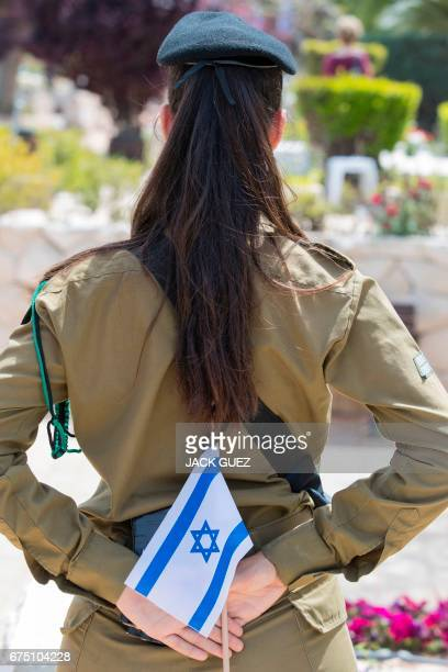 Israeli soldiers carrying the national flag stand at attention at the graves of killed comrades at the Kiryat Shaul military cemetery as the country...