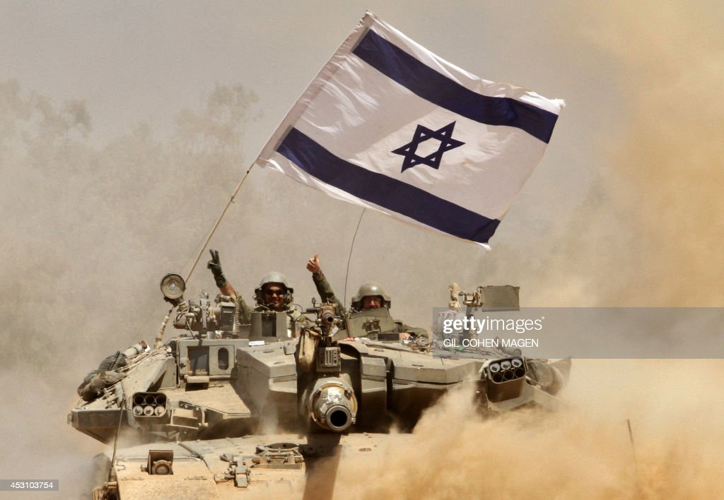 Israeli soldiers celebrate on their Merkava tank as they drive along the border between Israel and the Gaza Strip after they pulled out of the Gaza...