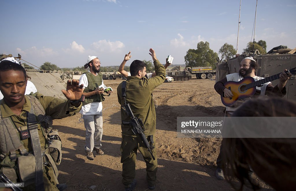 Israeli soldiers celebrate with ultra-Orthodox Jews as they prepare to leave a deployment area near the Israel-Gaza Strip border on November 22, 2012, a day after a cease fire was declared between the Jewish state and Hamas. Defence Minister Ehud Barak warned that Israel may resume its attacks on Gaza at any time if a truce that ended a week of bloodshed fails to hold. AFP PHOTO/MENAHEM KAHANA