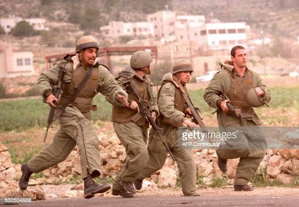 Israeli soldiers chase Palestinian stone throwers during clashes in the Hebron refugee camp of Al Fawwar 15 February where one Palestinian was shot...