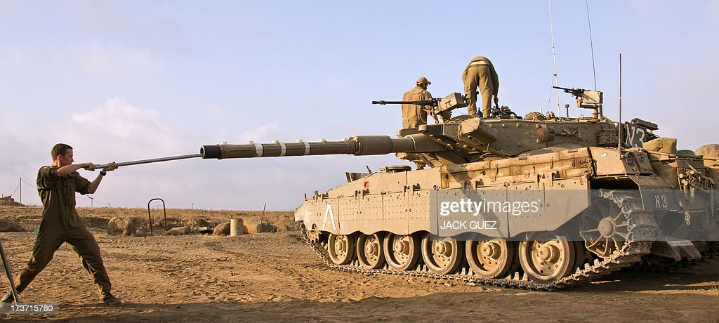 Israeli soldiers check a Merkava tank stationed in the Israeli-occupied Golan Heights along the border with Syria on July 17, 2013. Gunmen from Syria infiltrated a disused army outpost in the Israeli-occupied area of the Golan Heights just beyond the ceasefire line, a military spokeswoman said. The incident came a day after several mortar rounds hit the Israeli side of the Golan, causing several fires to break out along the ceasefire line as Syrian rebels battled regime forces near the Quneitra crossing.