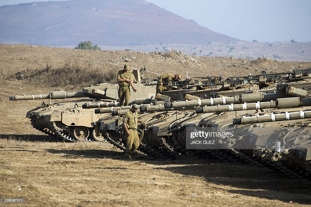 Israeli soldiers check a Merkava tank stationed in the Israeli-occupied Golan Heights along the border with Syria on September 1, 2013. The Israeli cabinet authorised on August 28 a partial call-up of army reservists amid growing expectations of a foreign military strike on neighbouring Syria, army radio reported. The unspecified number of troops are attached to units stationed in the north of the country, which borders both Lebanon and the Golan Heights.