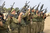 Israeli soldiers check their weapons at an army deployment area on the southern Israeli border with the Gaza Strip on August 1 after the proposed...