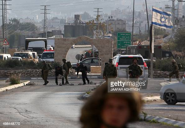 Israeli soldiers clear rocks placed by settlers in an attempt to block the road next to the site of an attack by a Palestinian who attempted to stab...