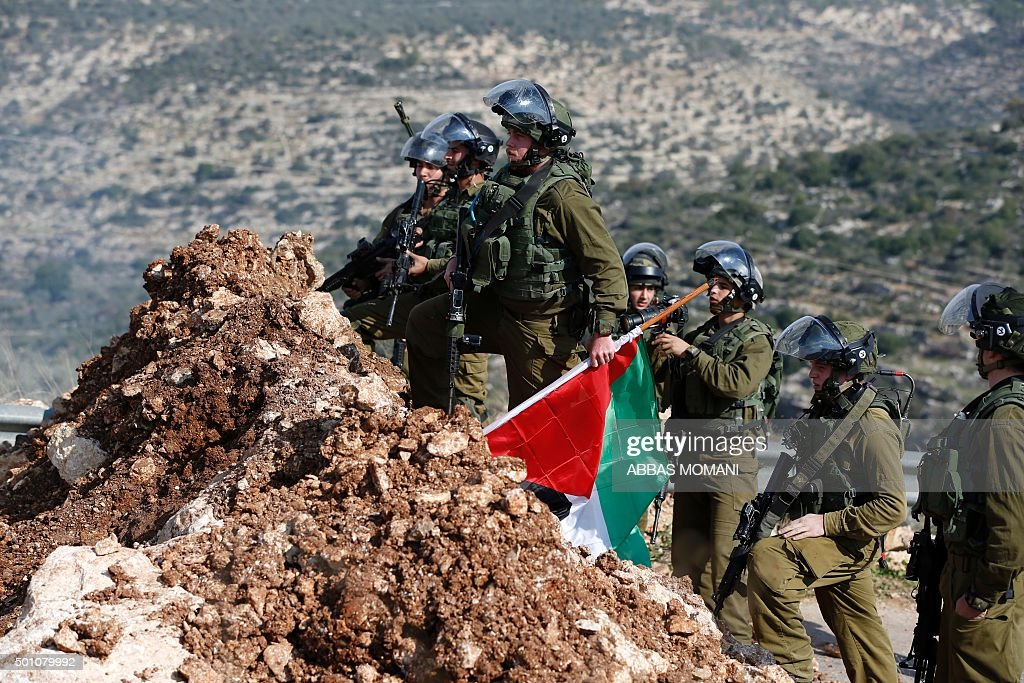 Israeli soldiers climb a mount where a Palestinian flag is planted during clashes with Palestinian protesters on December 12 2015 in the village of...