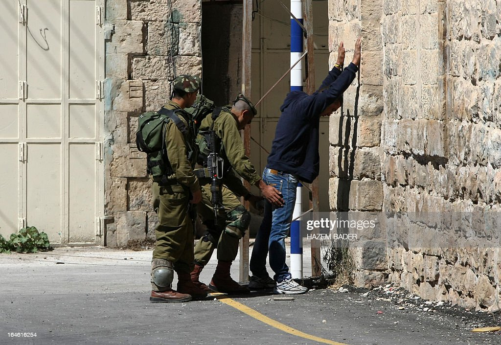 Israeli soldiers control a Palestinian man on his way to go home near the Ibrahimi Mosque and the Tomb of the Patriarch in the occupied West Bank city of Hebron on March 25, 2013. The Ibrahimi Mosque and the Tomb of the Patriarch will be closed to Muslims on March 27 and 28 due to the Jewish holiday of Pesach (Passover).