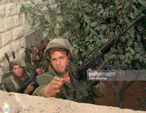 Israeli soldiers deploy in the garden of a Palestinian home October 4 2000 during riots in Ramallah in the West Bank The garden was used earlier by...