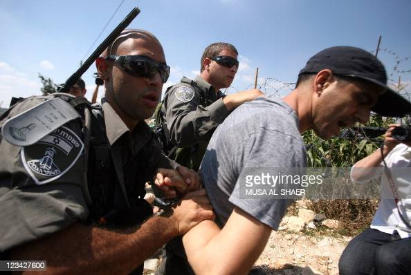 PLACE Israeli soldiers detain a Palestinian demonstrator during a protest against Israel's controversial separation barrier in the village of...