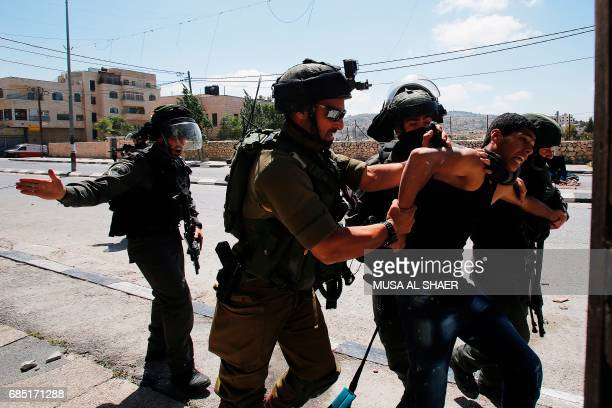 Israeli soldiers detain a Palestinian protester during clashes at the entrance of the West Bank city of Bethlehem on May 19 2017 / AFP PHOTO / Musa...